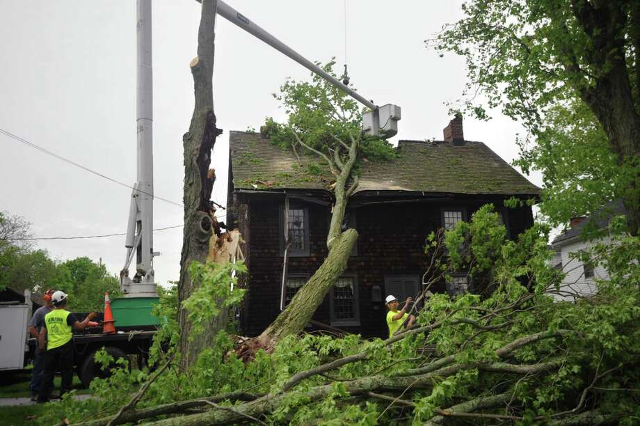 Arborists remove a large tree from the roof of an 18th century home at 62 Main Street in Newtown, Conn. on Wednesday, May 16, 2018  in the aftermath of Tuesday evening's storm. Homeowner Betsy Kenyon arrived home from work to discover the damage. Photo: Brian A. Pounds / Hearst Connecticut Media / Connecticut Post