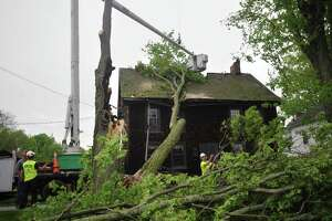 Arborists remove a large tree from the roof of an 18th century home at 62 Main Street in Newtown, Conn. on Wednesday, May 16, 2018  in the aftermath of Tuesday evening's storm. Homeowner Betsy Kenyon arrived home from work to discover the damage.