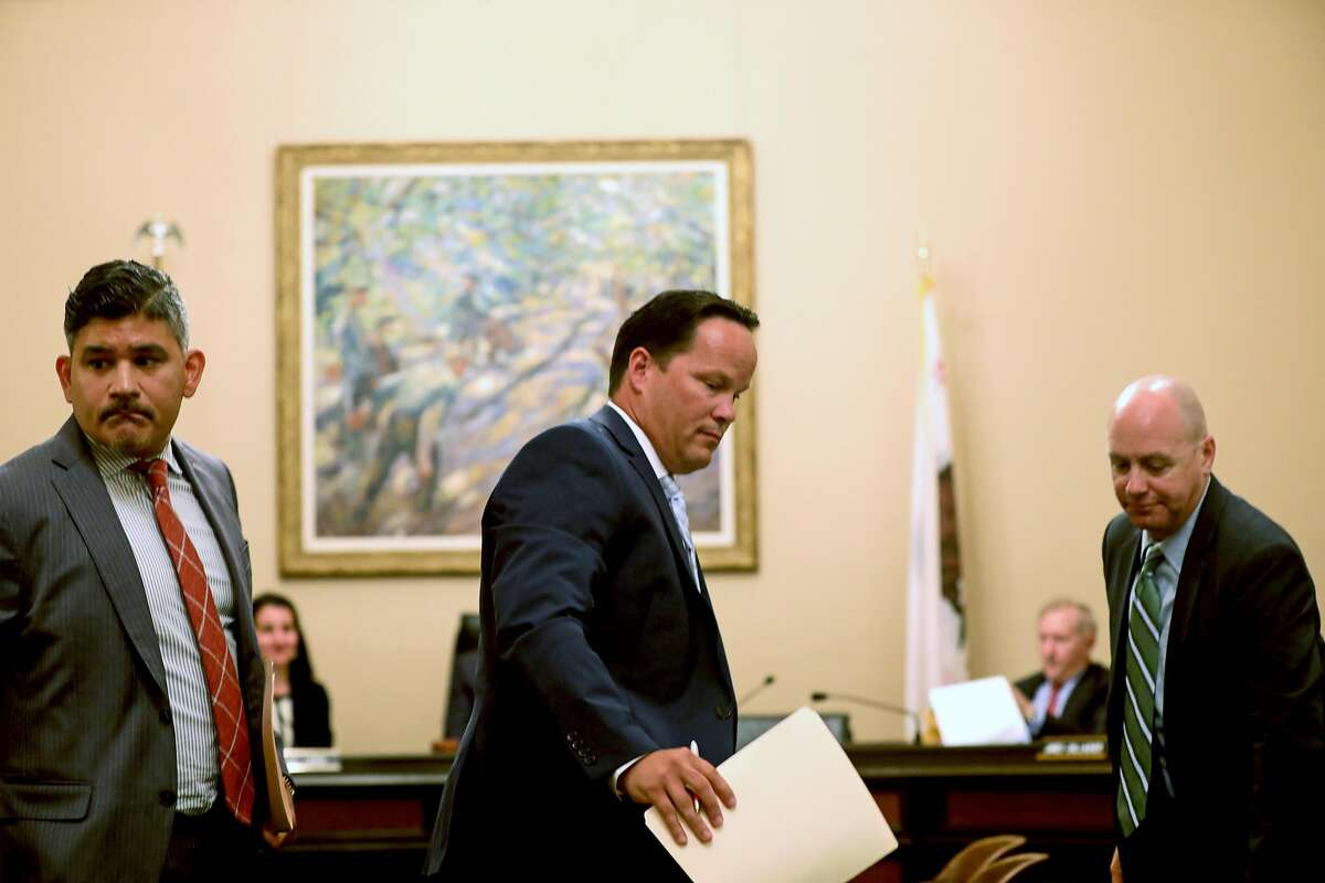(Left to right) Rudy Reyes, vice president and associate general counsel of the western region at Verizon, David Hickey, executive director of business sales and Wes Senechal, vice president - government sales, exit their seats after answering questions by the Assembly Select Committee in Sacramento.