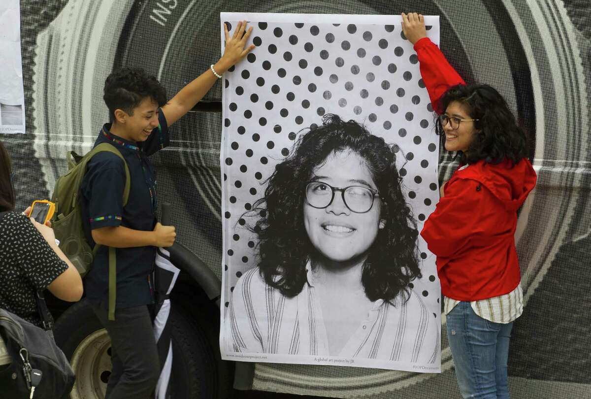 Charli Diaz, a student at the University of Houston Downtown, helps Sabrina Juarez, a University of Houston student, hold up a freshly printed poster of a photo the Inside Out Project's mobile photo booth had just taken of Juarez at the University of Houston, in 2017. The exhibit is intended to urge Congress to pass the DREAM act before the end of the year. It hasn't and the program's fate lies with the courts.