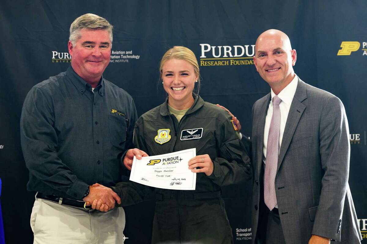 The Woodlands High School Air Force JROTC Cadet Maggie Marlow poses with Purdue University Chief Flight Instructor Jim Paulsen and Headquarters Air Force JROTC Director of Program Development Anthony