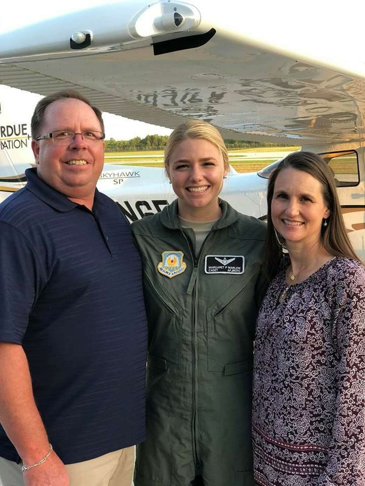 The Woodlands High School Air Force Cadet Maggie Marlow stands with her parents, Garth and Kristine Marlow, after earning her Private Pilot License at Purdue University.