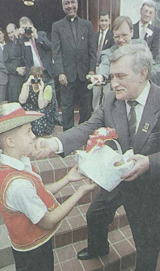 Lech Walesa, the former president of Poland, accepts a traditional Polish gift of bread and salt from Justin Halter, 10, outside of New Waverly's St. Joseph Catholic Church in October 1996. Photo: Houston Chronicle Photo