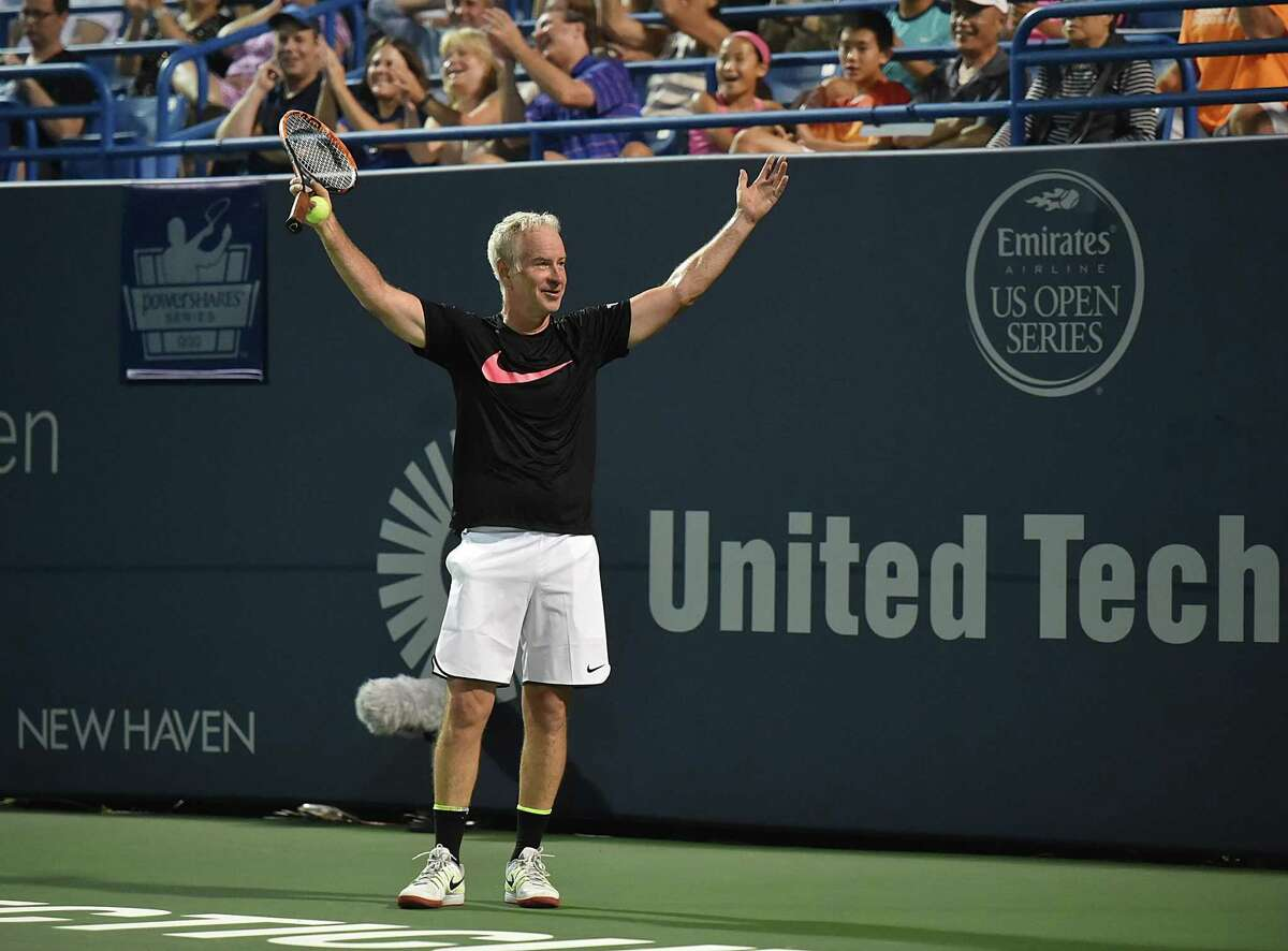 After seeing the replay, John McEnroe celebrates during the men's Legends match after challenging a call against James Blake in the 2016 Connecticut Open.