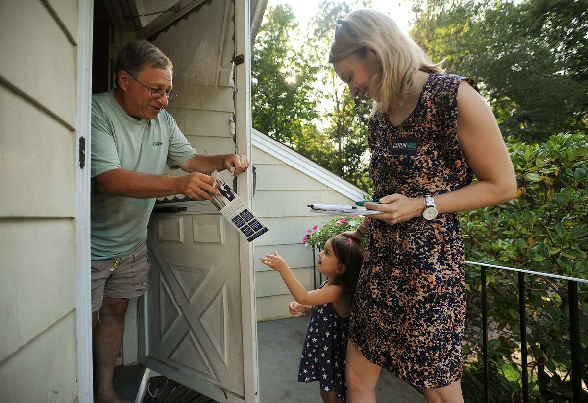 Rich Jacobs, of Fairfield, is handed campaign literature by Parker Pereira, 3, daughter of candidate for Fairfield state representative Caitlin Clarkson Pereira, during an afternoon of campaigning on Limerick Road in Fairfield on Wednesday. Clarkson Pereira was denied her request to the State Elections Enforcement Commission to use campaign funds to pay for child care.