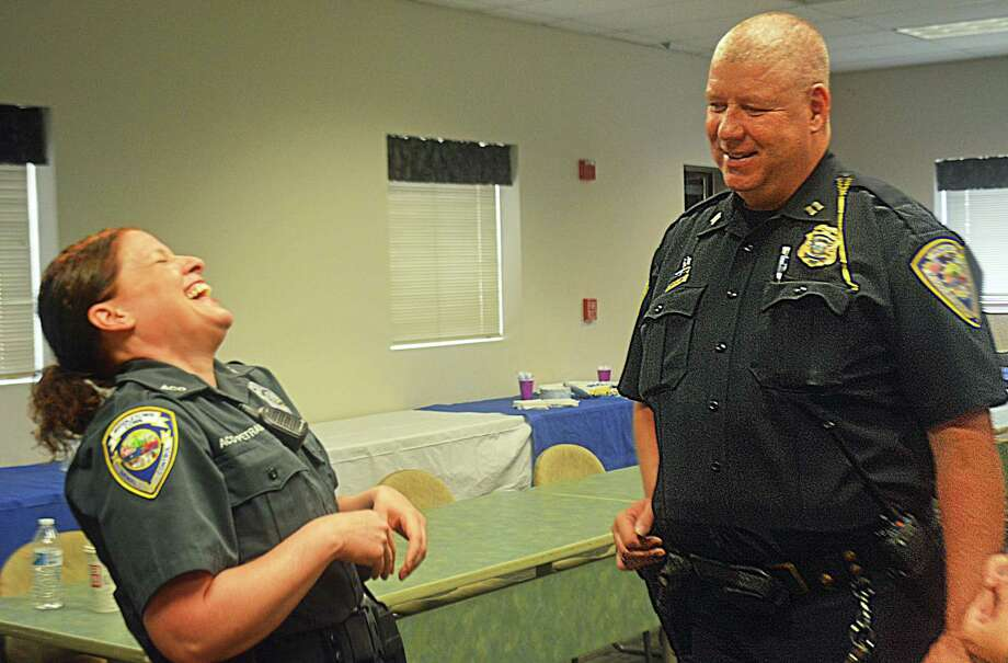 Middletown Police Capt. Sean Moriarty retired from the force Thursday with more than 31 years of service. His fellow officers, friends and family wished him good luck during a surprise going-away party in the community room Wednesday morning. Here, Moriarty shares a laugh with Middletown Animal Control Officer Gail Petras. Photo: Cassandra Day / Hearst Connecticut Media