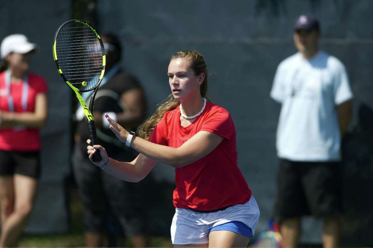 16-year-old Ally Buckley, of Hopkington, Rhode Island, runs towards the net to hit a volley during a USTA tennis clinic on the practice courts at the Connecticut Open in New Haven, Conn. on Friday, Aug. 24, 2018.