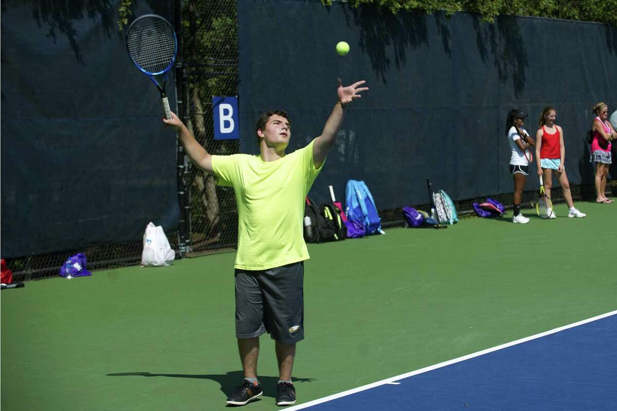 16-year-old Ethan Benoit, of Sheffield, Mass., serves during a USTA tennis clinic on the practice courts at the Connecticut Open in New Haven, Conn. on Friday, Aug. 24, 2018.