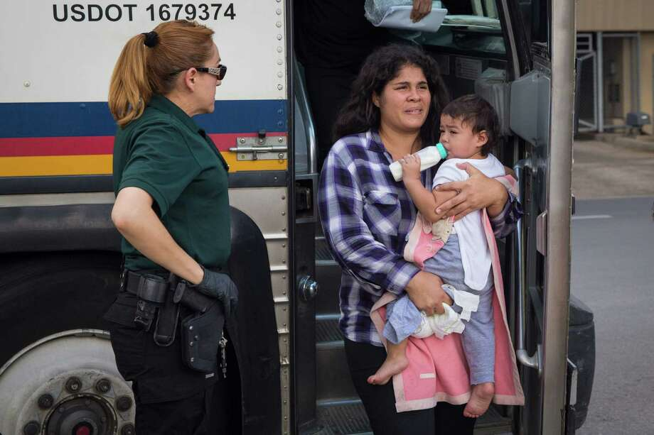 """PHOTOS: Busy along the borderA woman carries a baby in June 2018 as immigrants are dropped off at a bus station shortly after being released from detention through """"catch and release"""" immigration policy in McAllen, Texas. >>>See the immigration crisis through photographs ...  Photo: LOREN ELLIOTT, Contributor / AFP/Getty Images / AFP or licensors"""