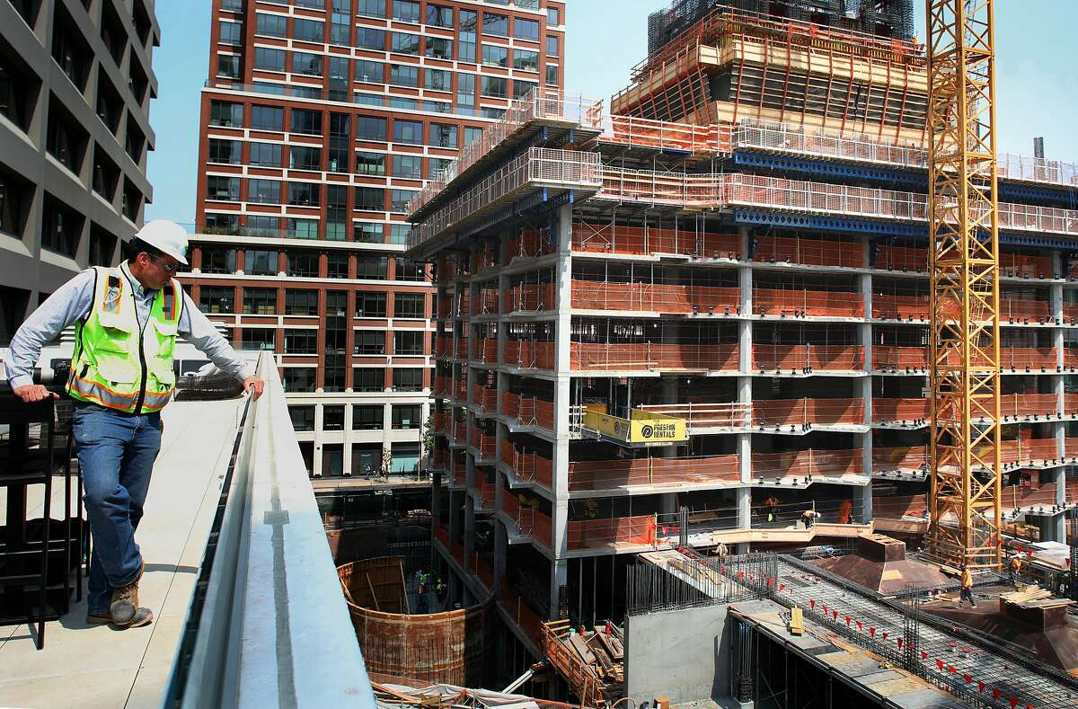 Lendlease construction senior superintendent Casey Curren shows present construction on 160 Folsom St. (right), a former parking lot near the Temporary Transbay Transit Center is where a condo tower is under constructionon Friday, Aug. 24, 2018 in San Francisco, Calif.