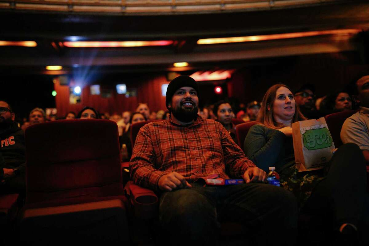 """Fred Padilla (left) and Anna Johnson watch the opening trailers before the start of """"Black Panther"""" on its opening day."""
