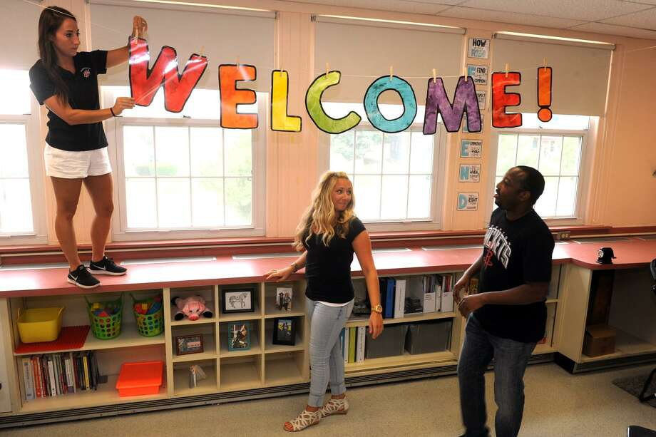 From left, social worker Samantha Aurelia, reading specialist Abbey Owens and school resource teacher Michael Benson hang a welcome sign in preparation for the new school year at Franklin Elementary School, in Stratford, Conn. Aug. 22, 2018. Photo: Ned Gerard / Hearst Connecticut Media / Connecticut Post