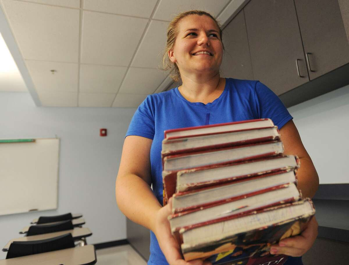 Teacher Luciana Coku-Rakaj brings an armload of textbooks to shelve as she prepares her seventh and eighth grade Spanish classroom at Derby Middle School in Derby, Conn. on Tuesday, August 21, 2018. Derby students first day of school is Monday, August 27.