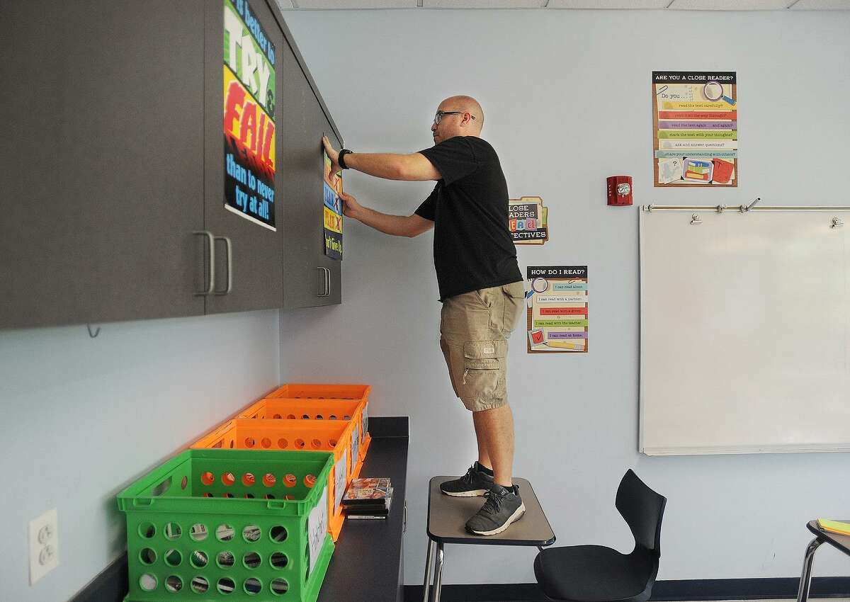 Teacher Dan Kreiness puts up posters as he prepares his seventh grade reading classroom for the new school year at Derby Middle School in Derby, Conn. on Tuesday, August 21, 2018. Derby students first day of school is Monday, August 27.