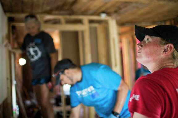Carol Lewis, Chris Sanchez and Stacy Lewis restore the drywall on the home of Alfredia Brooks who's house was severely water damaged during Hurricane Harvey. Stacy Lewis who is a professional golfer donated money to the project but also wanted to be able to work on the house as well, Thursday, Aug. 23, 2018, in Houston. About  40 volunteers will be working on the home to restore it in 24 hour.