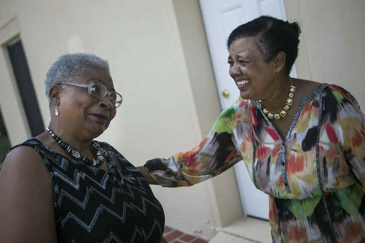 Karen Hudson gives Peggy Jones a face as they greet each other at the rededication of the restored mansion of African American political leader Charles M. Bellinger, Friday, Aug. 24, 2018.