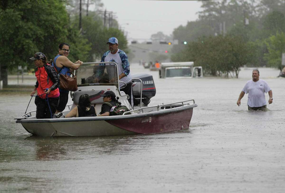 Neighbors with boats aid in rescues near FM 2351 and FM 518 Sunday, Aug. 27, 2017, in Friendswood.