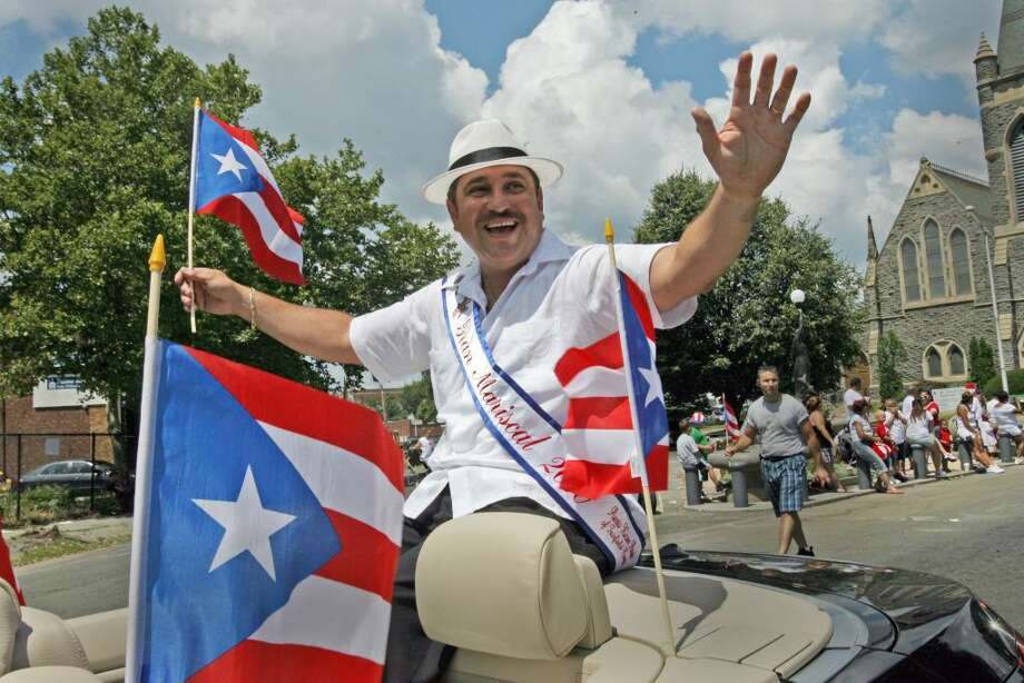 Grand Marshall Juan Santiago waves in the 17th annual Puerto Rican Day Parade in Bridgeport on Sunday, July 11, 2010. Photo: B.K. Angeletti / Connecticut Post