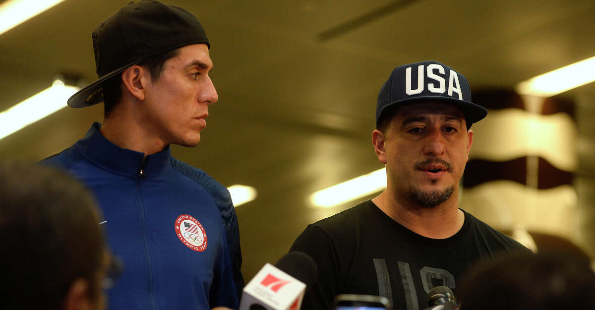 Steven Lopez, taekwondo athlete, listens as his brother and coach, Jean, talks to the media after they arrive home from the Rio Olympics at the George Bush International Airport in Houston on Tuesday morning. Photo taken Tuesday 8/23/16 Ryan Pelham/The Enterprise