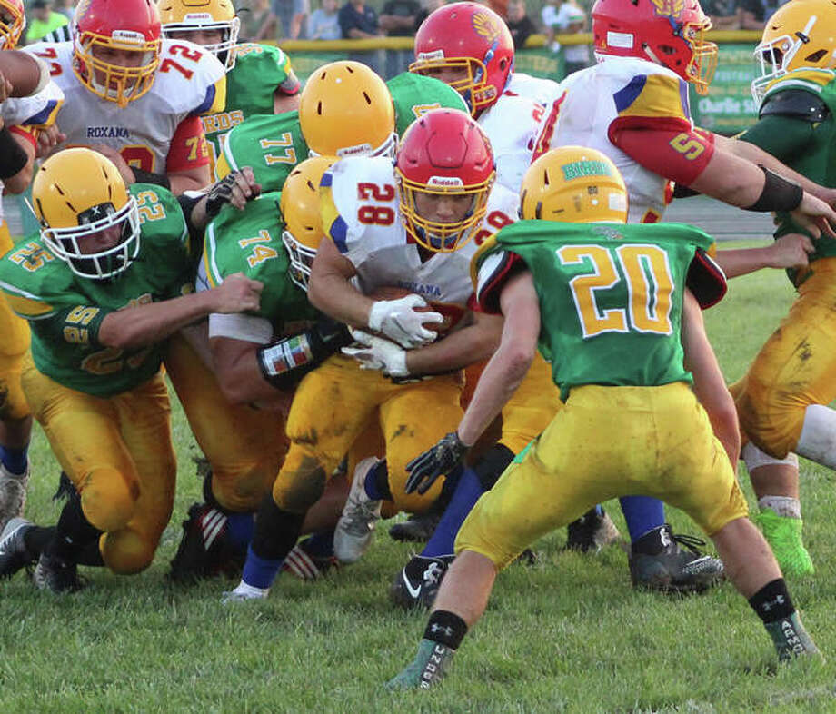 Roxana running back Michael Ilch carries some Piasa Birds tacklers while looking for more contact with Southwestern's Pauly Garrett (20) during Friday's South Central Conference game at Knapp Field in Piasa. Ilch rushed for 146 yards and two TDs on 30 carries in the Shells' 20-6 victory. Photo: Greg Shashack / The Telegraph