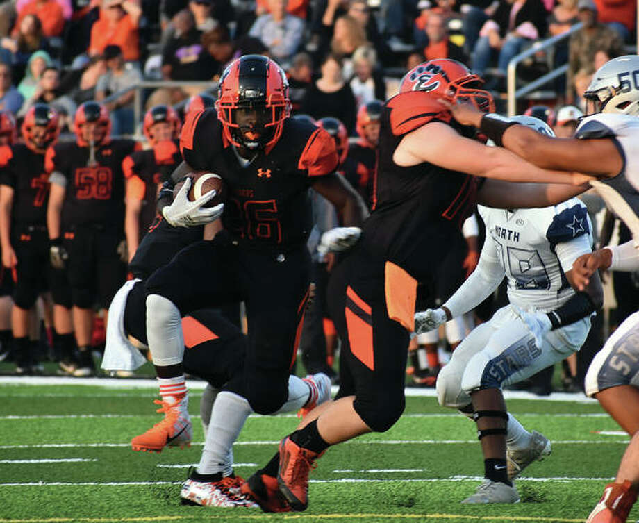 Edwardsville's Justin Johnson, left, runs around a block en route to a 10-yard touchdown in the first quarter.