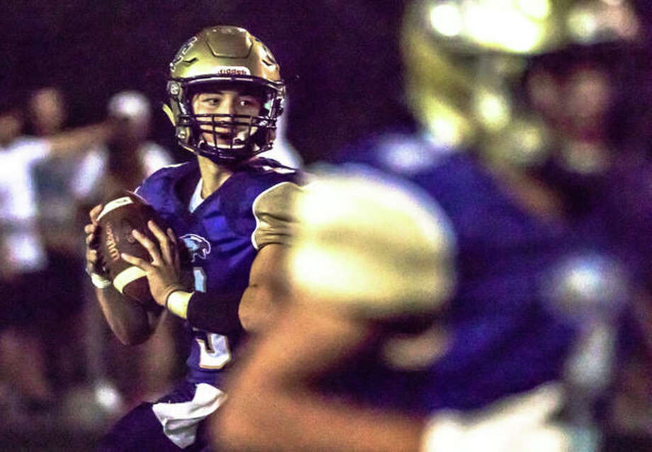 CM quarterback Noah Turbyfill looks downfield to pass Friday night against Marquette. Photo: Nathan Woodside | The Telegraph