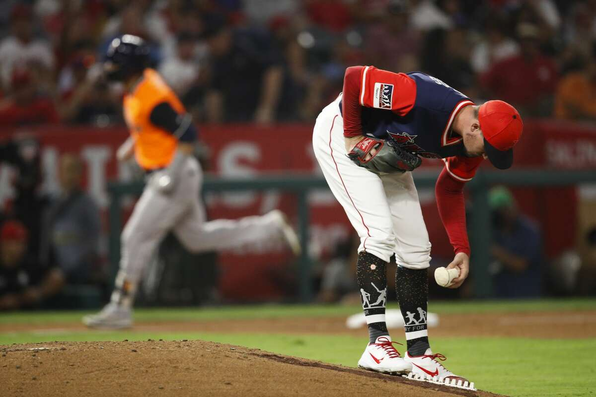 Los Angeles Angels starting pitcher Andrew Heaney picks up the rosin bag after giving up a grand slam to Houston Astros' Marwin Gonzalez, rear, during the fifth inning of a baseball game Friday, Aug. 24, 2018, in Anaheim, Calif. (AP Photo/Jae C. Hong)