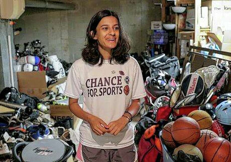 Anuva Shandilya shows some of the sports equipment she has collected through her non-profit organization, Chance For Sports, at her home in Naperville. Shandilya has collected something priceless to many kids in need: more than 3,400 pieces of sports equipment to donate so they can play. Photo: Bev Horne | Daily Herald (AP)