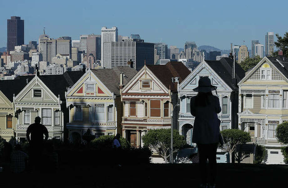 A woman looks toward a row of historical Victorian houses. The Trump administration has announced new rules aimed at preventing residents in high-tax states from avoiding a new cap on widely popular state and local tax deductions. Photo: Jeff Chiu | AP