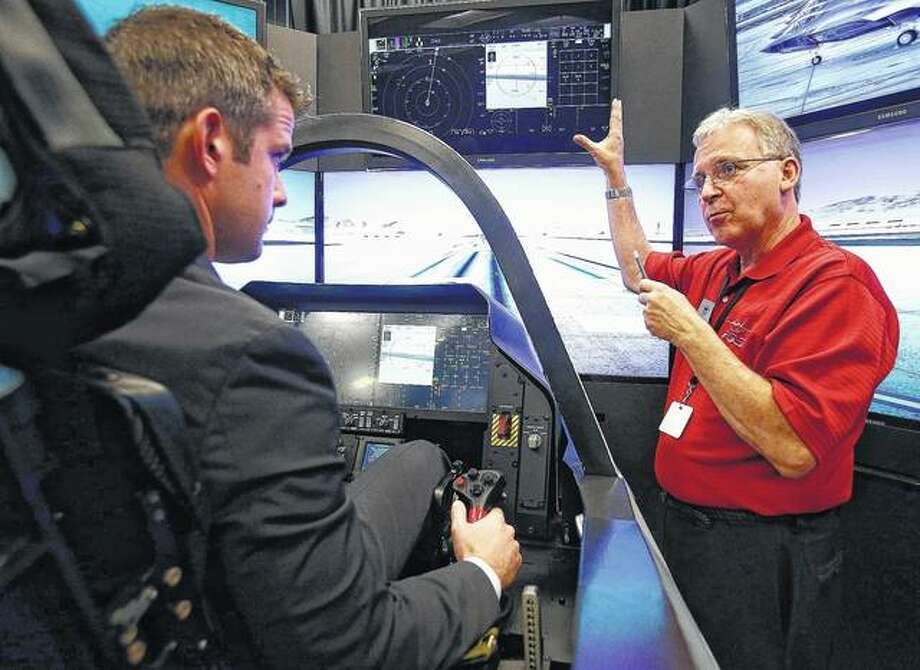 Lockheed Martin systems engineer Dennis Littrell (right) explains the instrumentation of the F-35 fighter jet simulator to U.S. Rep. Adam Kinzinger in 2013 in Rockford. Photo: Max Gersh | Rockford Register Star