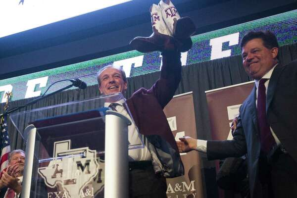 New Texas A&M University head football coach Jimbo Fisher is presented with Texas A&M cowboy boots by athletic director Scott Woodward during a press conference at the school's Hall of Champions at Kyle Field, Monday, Dec. 4, 2017, in College Station. ( Mark Mulligan / Houston Chronicle )