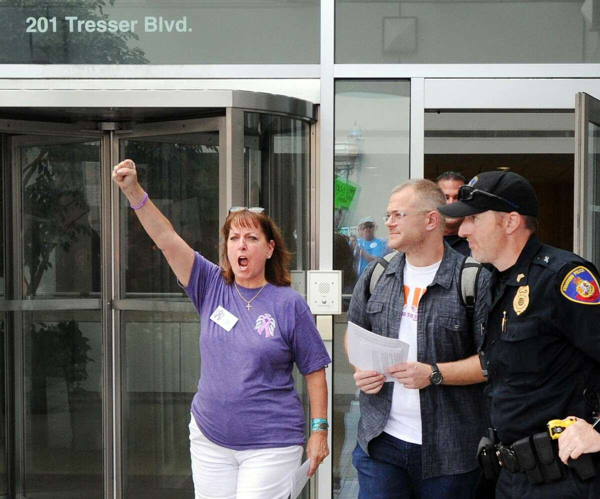 Protest organizer Cheryl Juaire pumps her fist in the air, after delivering a letter for Purdue Pharma's CEO Craig Landau, during a protest outside Purdue's headquarters at 201 Tresser Blvd., in downtown Stamford, Conn., on Aug. 17, 2018.