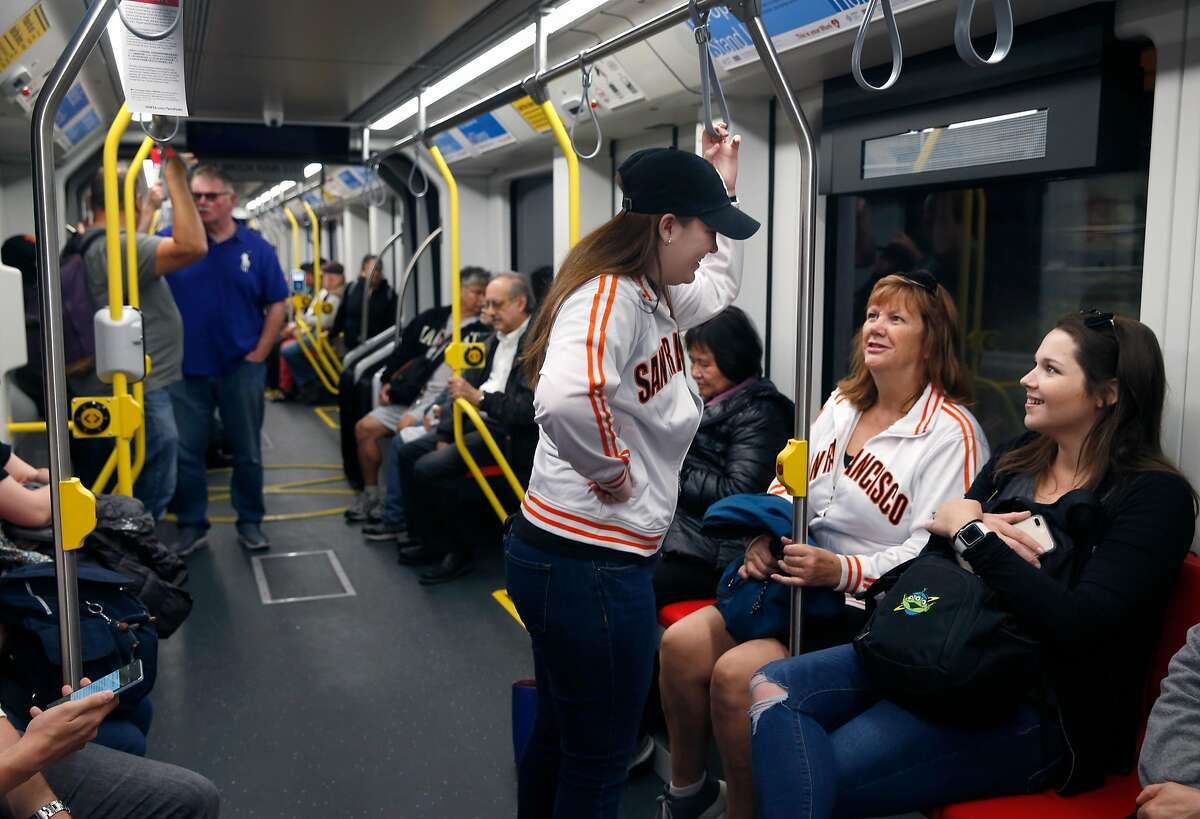 At right, Katelyn Stanley rides a T-Third light rail vehicle from the West Portal Muni Metro station to AT&T Park with her wife Lauren Stanley (left) and Nola Armour (center) in San Francisco, Calif. on Saturday, Aug. 25, 2018. The SFMTA reopened the Twin Peaks tunnel to light rail service Saturday following a two-month closure for an extensive restoration project.