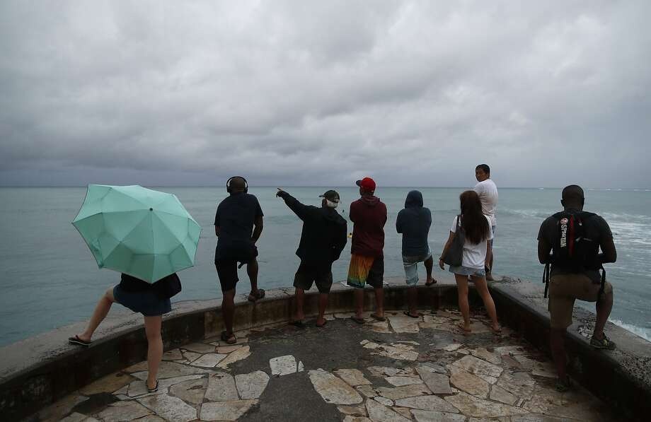 FILE PHOTO: People look out over the ocean along Waikiki Beach in a light rain from a troical storm, Saturday, Aug. 25, 2018, in Honolulu.  Photo: John Locher / Associated Press