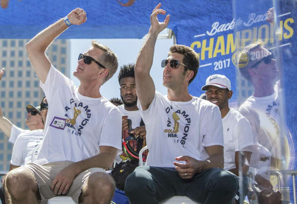 Warriors' head coach Steve Kerr and general manager Bob Myers wave to construction workers watching as they participate in an NBC Bay Area Sports question and answer session with the team and coaches before the start of the Golden State Warriors NBA Finals victory parade in downtown Oakland, Calif. Tuesday, June 12, 2018.