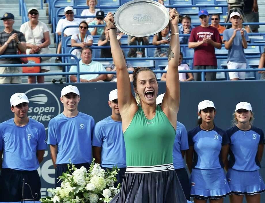 Aryna Sabalenka raises the trophy above her head to celebrate her victory over Carla Suarez Navarro in the Connecticut Open final no Saturday. Photo: Catherine Avalone / Hearst Connecticut Media / New Haven RegisterThe Middletown Press