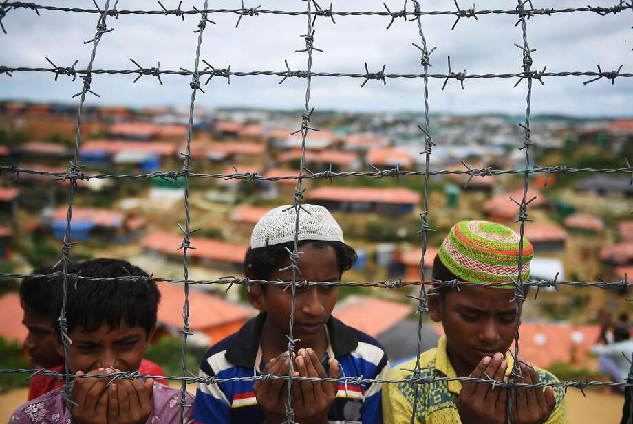 Rohingya refugees from Myanmar pray during a ceremony in August at a camp in Ukhia, Bangladesh. More than 700,000 have fled Myanmar since last year to escape deadly violence. Photo: Dibyangshu Sarkar / AFP / Getty Images