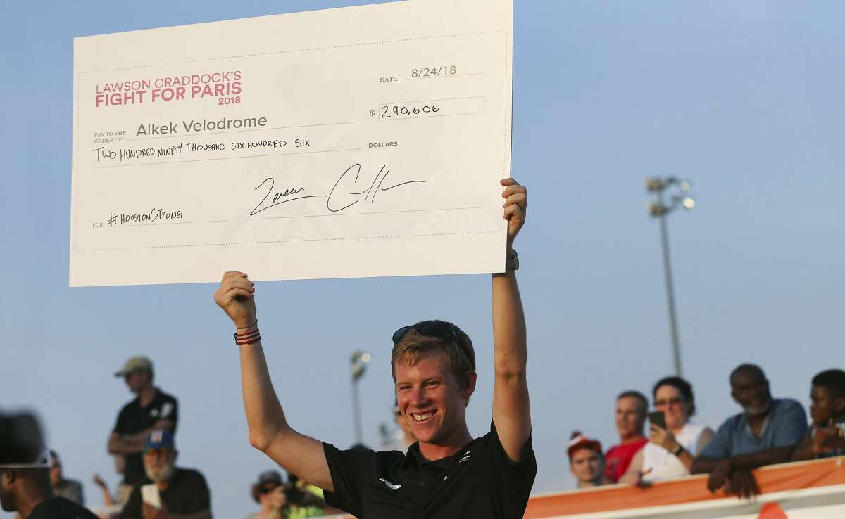 2018 Tour de France last place finisher Lawson Craddock,h holds up a check of money he raised for the Alkek Velodrome which was damaged from Harvey on Friday, Aug. 24, 2018 in Houston. Craddock turned his accident on the first day of the tour into a motivation for raising money for the velodrome, where he first started cycling.