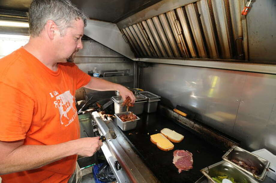 Steve Walker of Jerseyville cooks inside his Pig on a Wing truck. Photo: David Blanchette | For The Telegraph