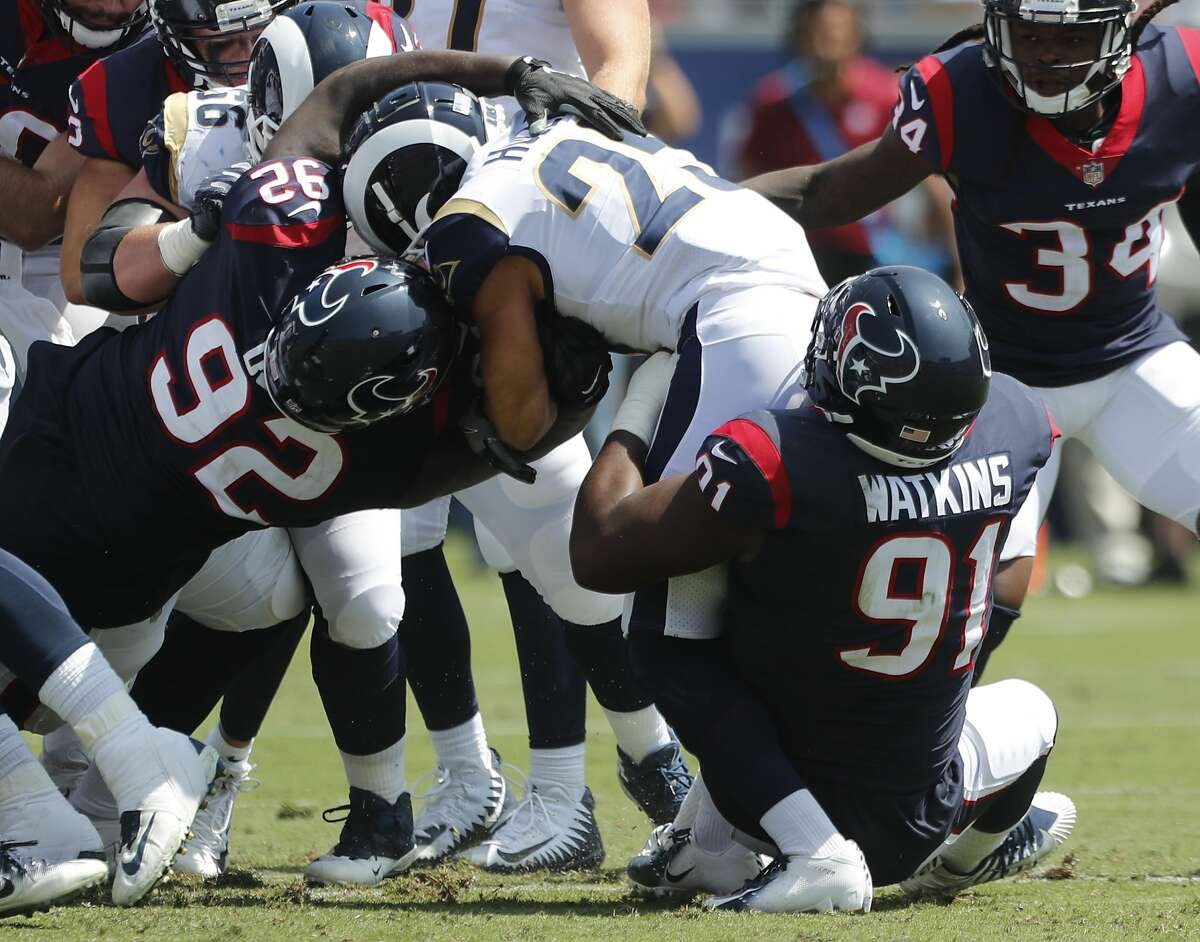 Houston Texans defensive tackle Brandon Dunn (92) and defensive end Carlos Watkins (91) stop Los Angeles Rams running back Nick Holley (25) during the second quarter of an NFL preseason football game at the Los Angeles Memorial Coliseum on Saturday, Aug. 25, 2018, in Los Angeles.