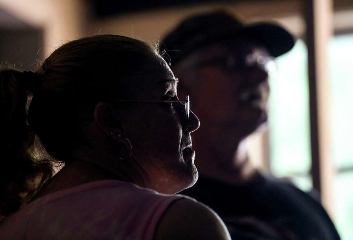 Suzan Trout, and her husband Daniel Trout, talk with volunteers as they repair their Hurricane Harvey-damaged home, Thursday, July 26, 2018, in Houston.