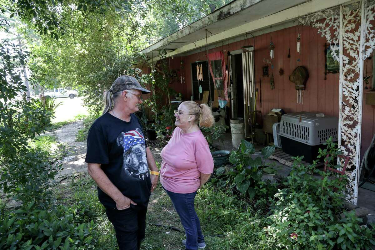 Daniel Trout jokes with his wife of 33 years, Suzan Trout, as their home, which was damaged during Hurricane Harvey is repaired by volunteers, Thursday, July 26, 2018, in Houston.