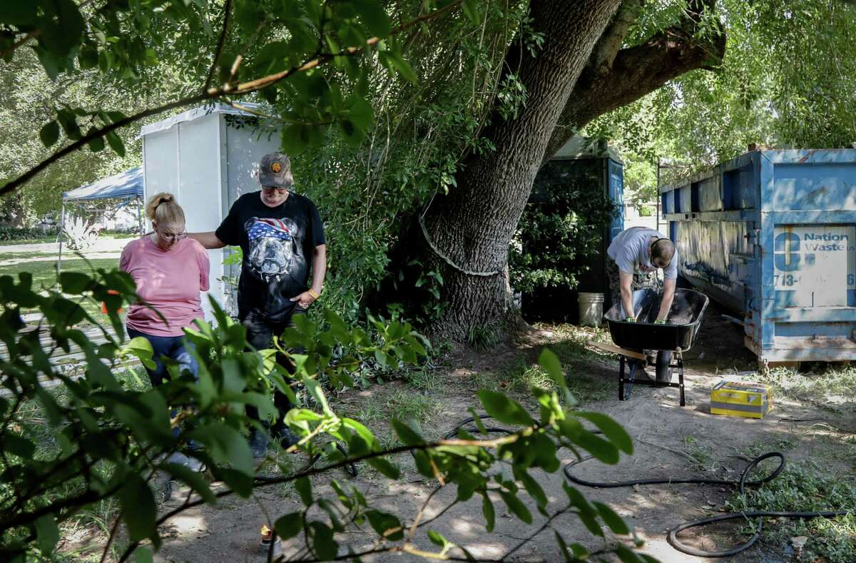 Daniel Trout and his wife Suzan Trout walk around their half-acre property, as their home is repaired by volunteers, including Jason Asnes, pictured at right, Friday, July 27, 2018, in Houston. The Trout's home was damaged during Hurricane Harvey.