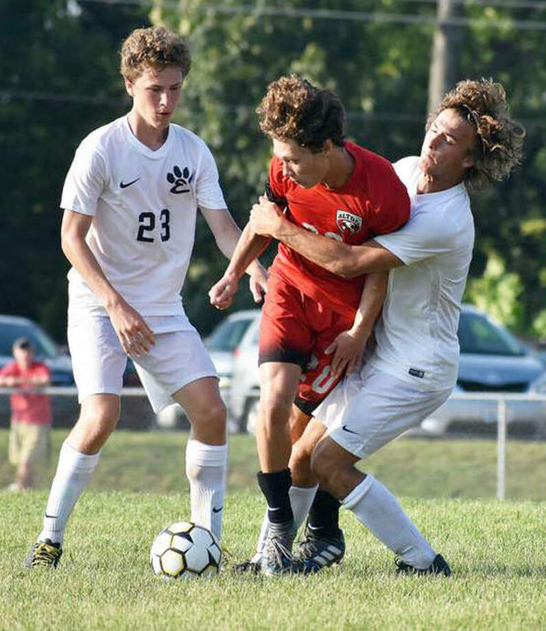 Edwardsville's Kadin Lieberman, right, wraps up Alton's Joe Morrissey in Saturday night's final game of the Alton Redbirds Round-Robin Tournament at Alton High school. Edwardsville's Andrew Mills (21) is also pictured. Photo: Matthew Kamp | For The Telegraph