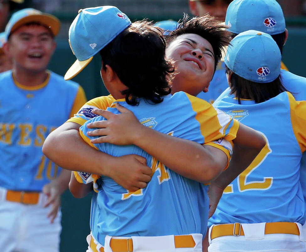 Honolulu, Hawaii's Sean Yamaguchi, right center, hugs Ka'olu Holt as they celebrate getting the final out of the United States Championship baseball game against Peachtree City, Georgia at the Little League World Series tournament in South Williamsport, Pa., Saturday, Aug. 25, 2018. Hawaii won 3-0 and will face South Korea in the Little League World Series Championship game Sunday. (AP Photo/Gene J. Puskar)