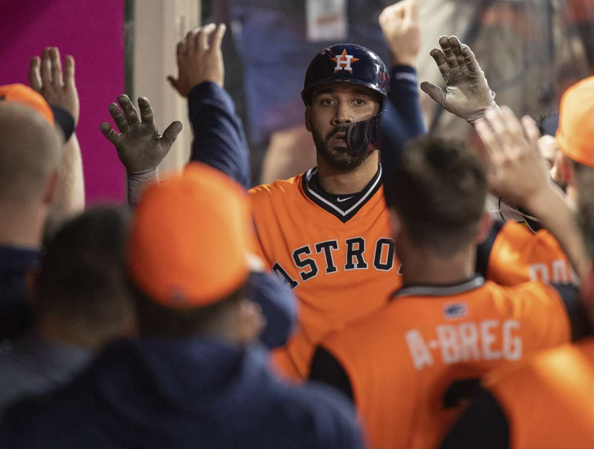 Houston Astros' Marwin Gonzalez is welcomed in the dugout after hitting a solo home run during the eighth inning of a baseball game against the Los Angeles Angels in Anaheim, Calif., Saturday, Aug. 25, 2018. (AP Photo/Kyusung Gong)