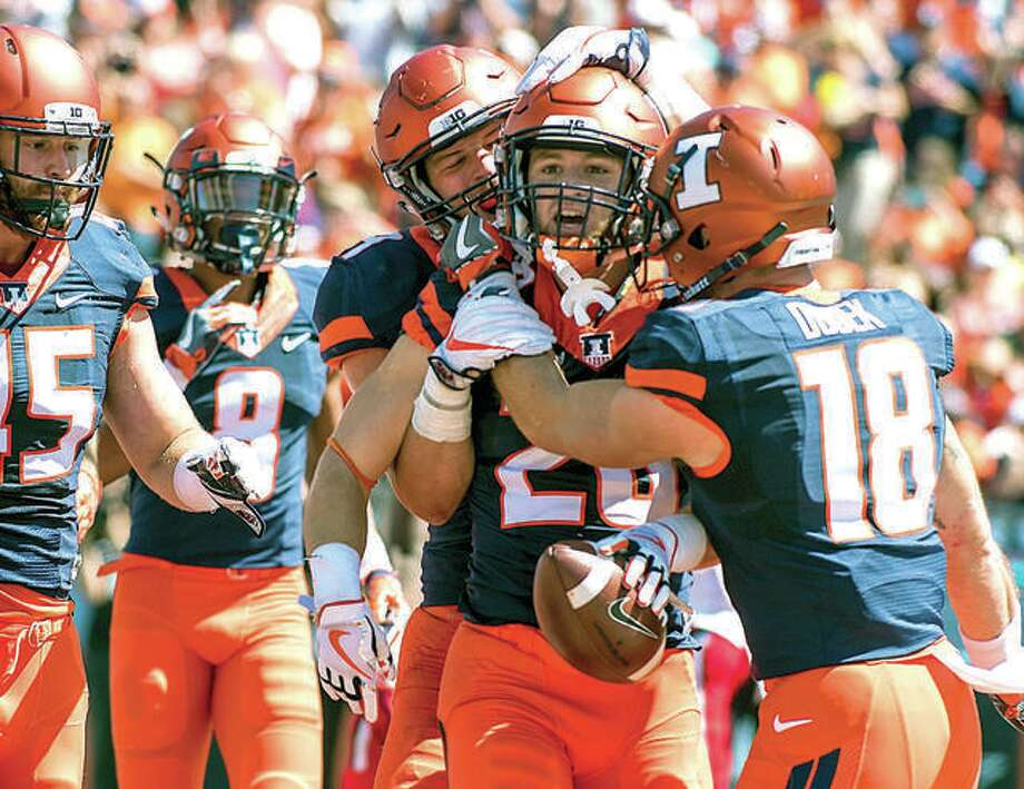 Illinois running back Mike Epstein (26) is congratulated by teammates after a touchdown run last season against Ball State at Memorial Stadium in Champaign. Photo: AP