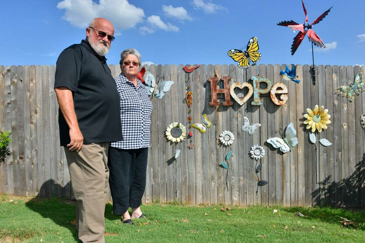 Tim and Sharlotte Mott stand in front a portion of their fence that is a memorial to their daughter Julie, who's corpse vanished three years ago.