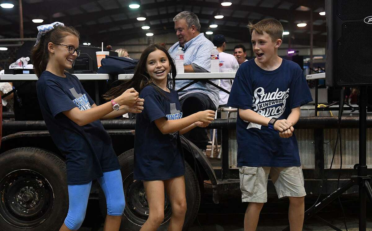 Creekwood Middle Schoolers Briley Campbell, 11, from left, the daughter of KHS Head Football Coach Barry Campbell, Hayley Tappan, 11, and Matt Morris, 12, the daughter of KHS Student Council Co-Advisor Amy Morris, show off their dance moves at the Humble ISD Pep Rally for the community kicking off the district's Centennial Year Celebration in the arena at the Humble Civic Center on August 25, 2018.