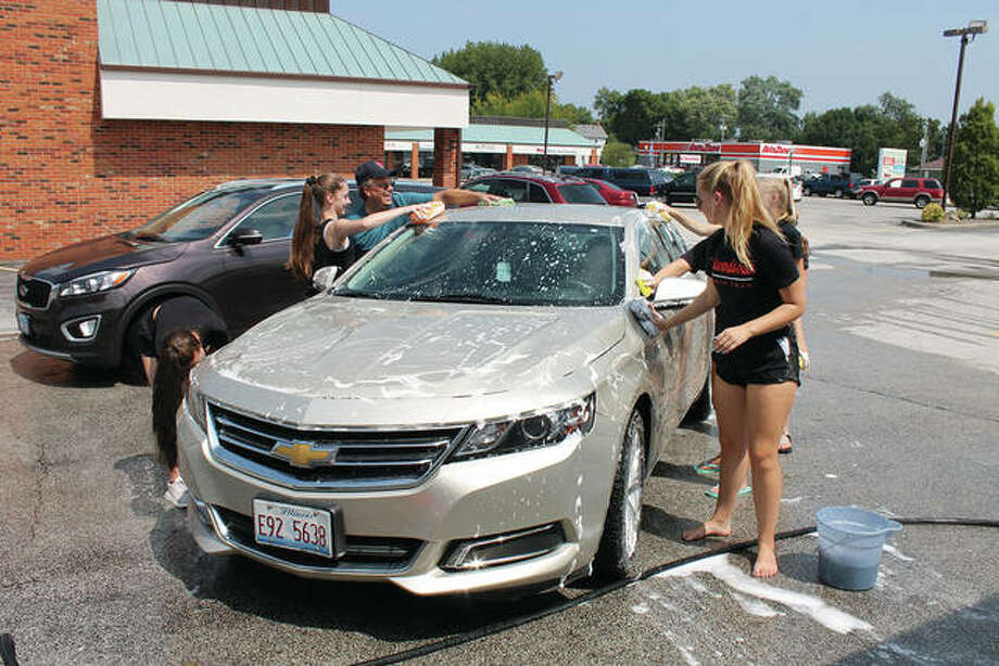 Less than 12 hours after performing at the Edwardsville High School football game, the EHS dance team was up early on Saturday, conducting a car wash fundraiser at Joe's Market Basket. Dance team members and parents washed cars for four hours, also selling Krispy Kreme doughnuts at the event. Photo: Bill Tucker/Intelligencer